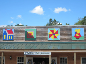 These 4 small barn quilts are on the Women's building at the Badger Steam and Gas Show located just off Hwy. 33 at S3347 Sand Rd., Baraboo, WI.  Earl Sprecher's four daughters Jean, Judy, Janet and Joanne chose patterns and painted them for the building. They represent the following: #1 – Sunbonnet Sue Jean Sprecher Brew chose this pattern as she collects Sunbonnet Sue quilts.  #2 – Windmill Judy Sprecher Wehler chose this pattern as she lives on the Sprecher family farm which has a windmill.  #3 – Log Cabin Janet Sprecher-Bruski chose this pattern as she hopes to live in a log cabin some day.  #4 – Schoolhouse Joanne Sprecher Welty of Milwaukee, WI chose this pattern as she is the youngest in their family and is always a student of some sort.