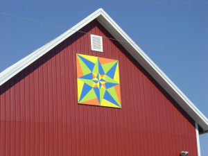 At S40654 State Road 136, Reedsburg, WI you will find this barn quilt. Belonging to Brian & Dena Bender this quilt pattern is triple star. This was painted by the Reedsburg Middle School Art Class as a gift to Dena for her 14 years working at their school. She quit that job and went farming full-time with her husband, Brian in October 2011. The gift was given to her when they opened their farm to the public for the Sauk County Dairy Breakfast in June 2012.