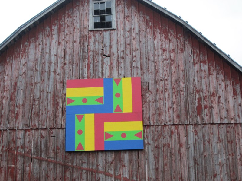 This barn quilt is on the Mike and Jodi Cook-Husom farm in North Freedom on Denzer Road. The rail fence pattern was picked out by their mother, Patty Cook.  It was a gift to their mother and father, Monte, for their anniversary in 2011 from daughters Sara and Jodi.  To get to this barn quilt, turn on to Bender Drive from Denzer Road. (North Freedom area)