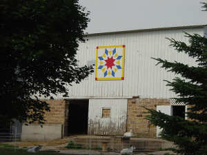 "Barn Quilt Installed on Enge Farm  The newest barn quilt in Sauk County was recently installed on the Mike and Rhonda Enge barn on their homestead located of Hwy. PF at S9106 Hager Road, Prairie du Sac.  The quilt pattern chosen by Rhonda Enge is called the ""Harvest Sun"" and is very fitting for their family as they have 3 boys; Travis, Dusty and Dan, who all enjoy the large family dairy farm.   They Enge operation has an extensive amount of crop land and it is truly the harvest sun that assists them with their success each year.   The red, blue, white and yellow colors are visible from many miles around as you head East toward their farmette on Hwy. PF or South on Denzer Road (Gasser's hill).  Take a drive and enjoy the beautiful agricultural landscape as you look for this bright quilt on their white barn with their donkey and sheep relaxing beneath the quilt."