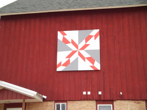 "A restored barn used to build performance engines—""it needs a bit of a woman's touch in a man's way"" is what Jenny Frey said when she offered to sponsor a Sauk County barn quilt.  Her woman's touch was a barn quilt as she admires them on their way to tractor pulls which both her and her husband, Dennis, are involved in.  They love the Allis Chalmers so that is where the colors of their barn quilt came from.  She chose the ""Hunter's Star quilt pattern using Allis Chalmers orange and gray along with some white as they are big hunters in the fall.  As you drive down Hwy. 60 or Cty Rd B, Sauk City, you will see their barn sitting on the corner and the quilt installed right above their shop entry.   Jenny states, ""The guys now understand how it represents us and I told them a little culture doesn't hurt them"" (and then they were back to talking deer hunting).  So take a drive down Hwy. 60 and enjoy the Hunter's Star on the Fair Valley Performance barn at the corner of Hwy. 60 and B."