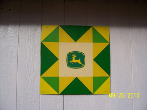 In 2010, Nancy Getschman painted this smaller barn quilt and placed it on their garage located at 1805 W. Pine St, Baraboo, WI.  On their way to the Old Threshers Reunion in Mt. Pleasant, IA they admired the many barn quilts along the route and decided to paint one for their barn.  Not knowing what to do they looked up directions on the internet.  Next year they plan on making another one for the other side of the barn which can be observed from the new four lane Hwy. 12.  Every year Gale and Nancy sponsor a Tractor Ride the second weekend in June.  They chose this weekend because their first stop is the Sauk County Dairy Breakfast.  Information on the ride can be found at http://www.tractorride.org/