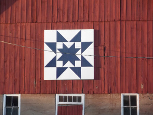 "The ""Rising Star"" quilt pattern from 1929 used on the Orlo Peetz farm is one of the most common.  This was chosen by owner Victoria Peetz and painted by them and hung in  June of 2011.  Orlo and Victoria bought the farm in 1973 and raised purebred Duroc hogs.  In 2001 they built a home on Pine Meadow Road and retired from raising hogs.   The farmland is currently rented out and corn and alfalfa are normally raised on the land.  E10498 Cty Rd. PF, Prairie du Sac, WI"